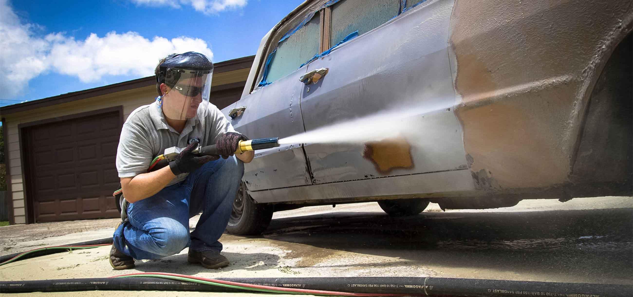 man blasting paint off old car