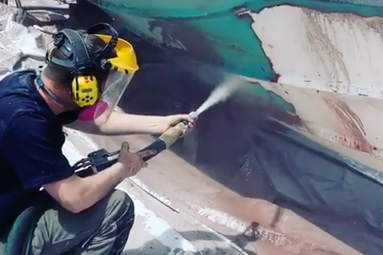 man removing antifouling paint from a boat hull