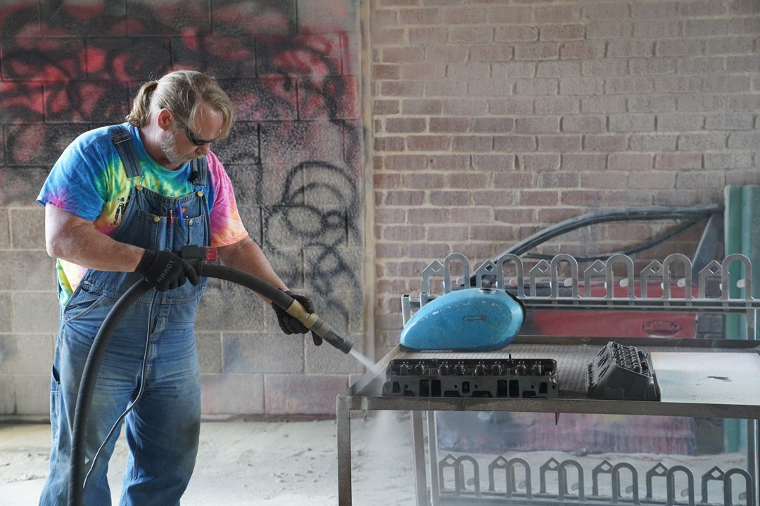 man in tie dye shirt removing paint from motorcycle fuel tank