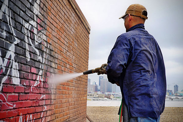 graffiti being cleaned off brick