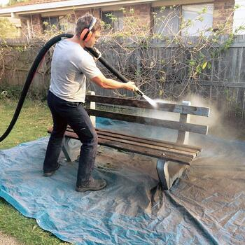 abrasive blasting the grime and paint off a wooden bench