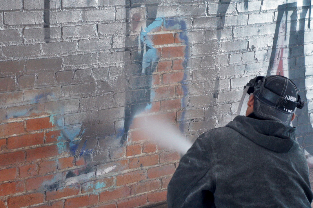 graffiti being removed from antique brick