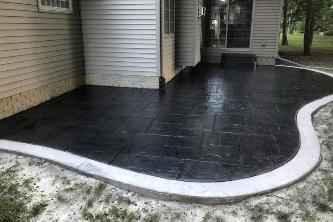 black sealer freshly applied to concrete patio