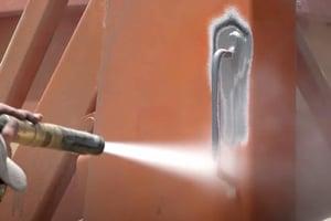 abrasive blasting orange paint off heavy equipment