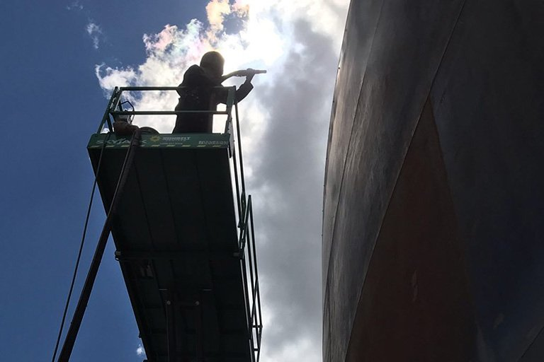 silhouetted man abrasive blasting a large tank