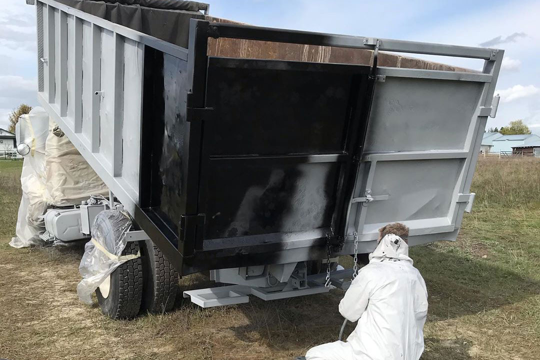 man applying black paint to a freshly blasted dump bed
