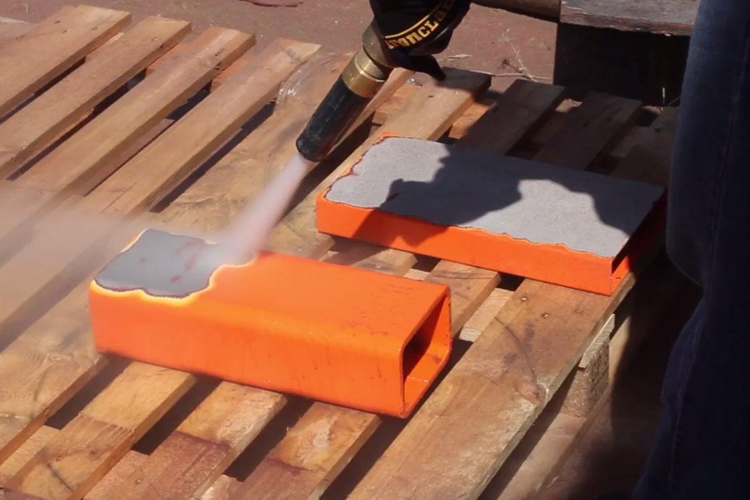 orange powder coat being sandblasted