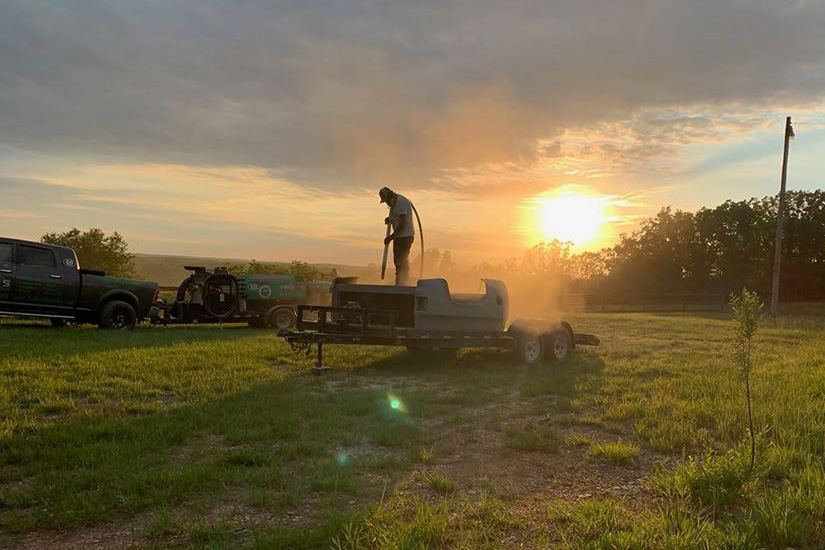 sandblasting a trailer at sunset