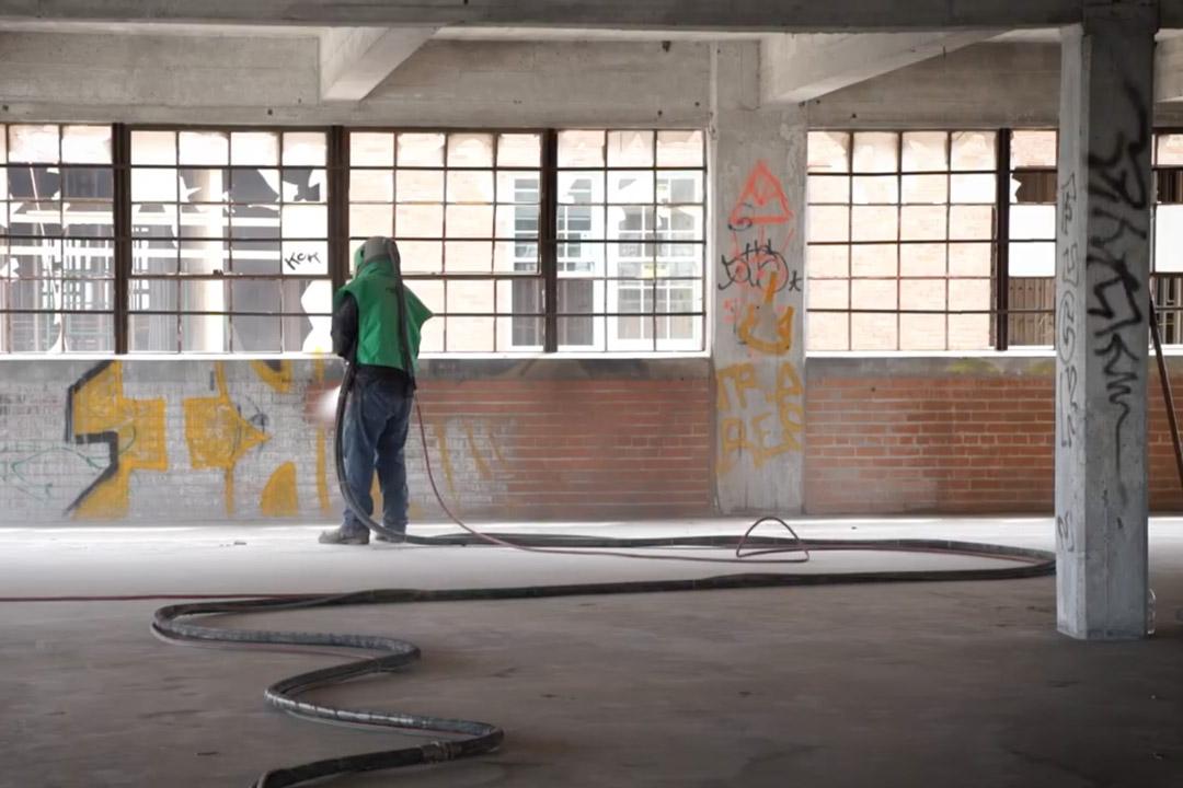 man in green respirator removing graffiti in a brick building