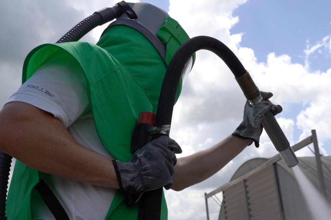 man wearing nova 3 and holding blast hose