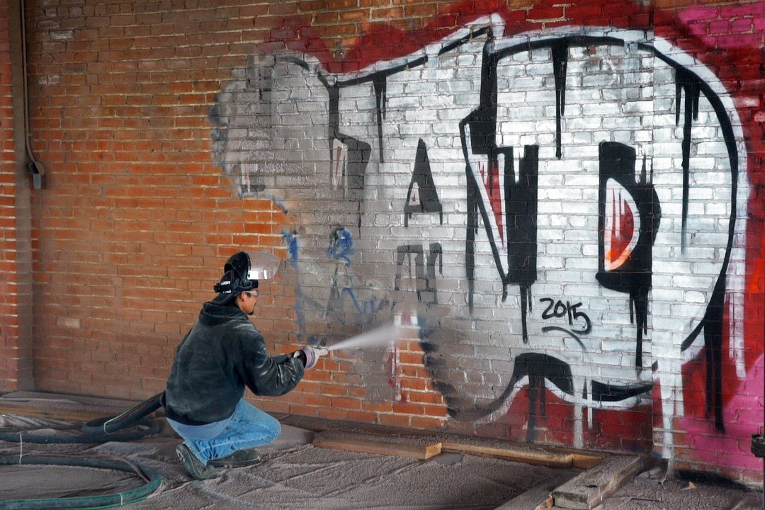graffiti bring removed from brick wall with dustless blasting
