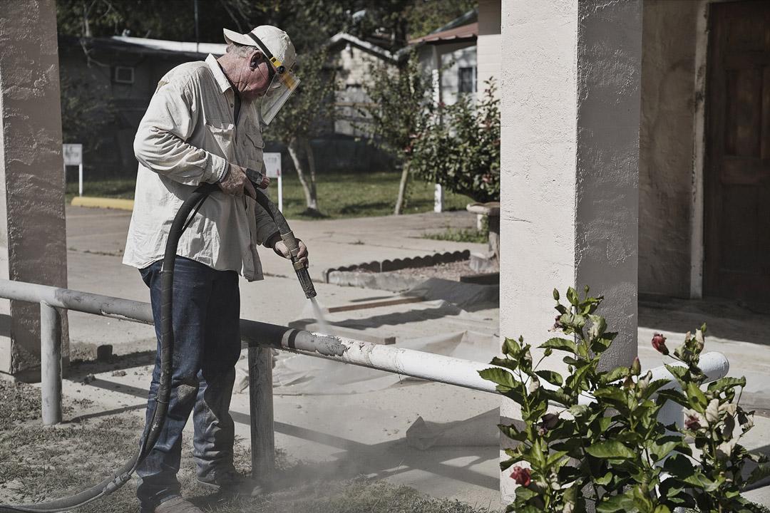 man sandblasting white paint from metal rail