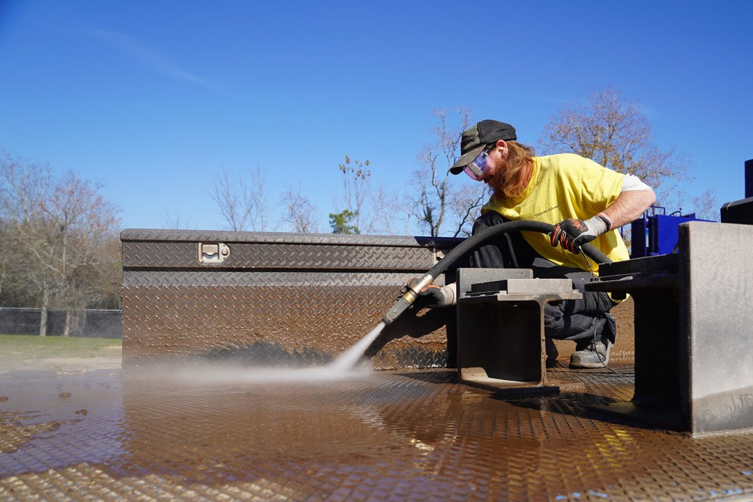 man in yellow shirt abrasive blasting a trailer bed