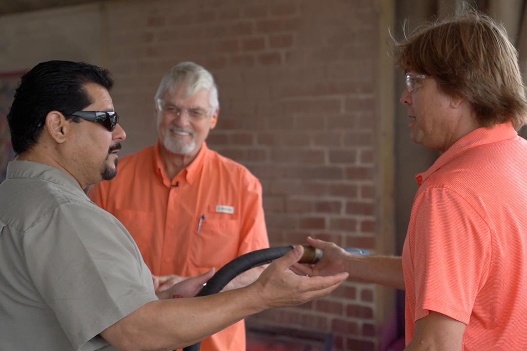 three men talking and holding sandblasting hose