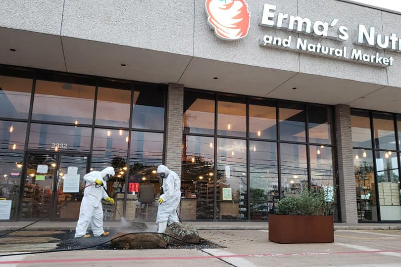two men in hazmat suits applying vapor disinfectant at a store