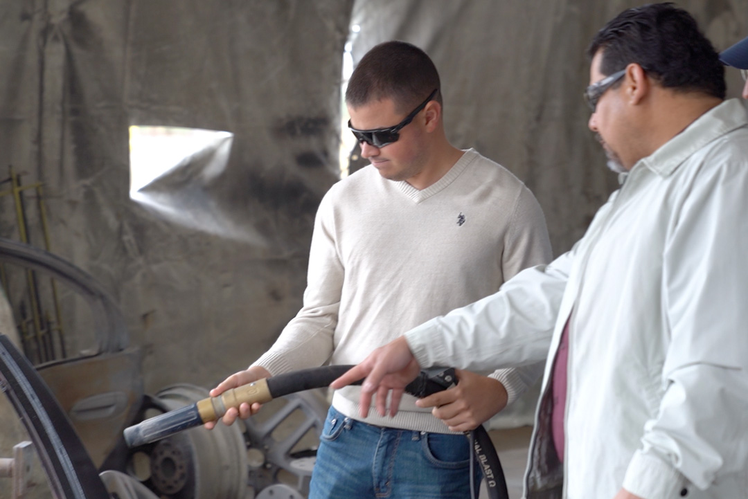 two men in white shirts holding hose