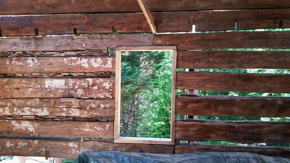 brush blasting the interior of a log cabin
