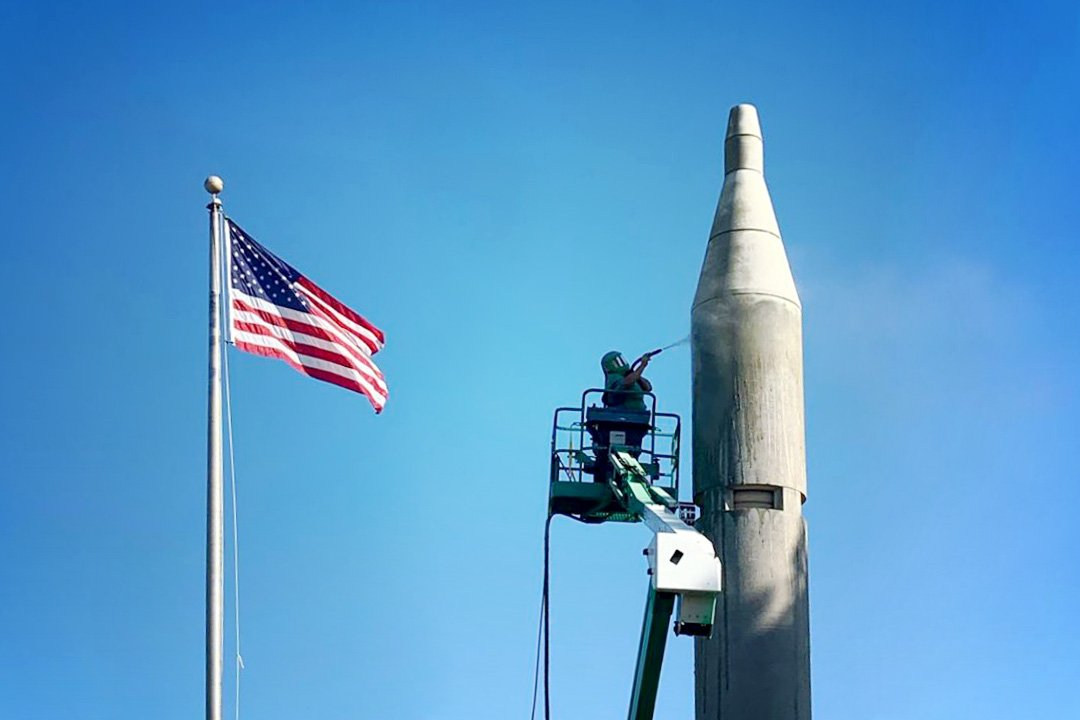 Abrasive Blaster on lift cleaning the top of a rocket with american flag in background