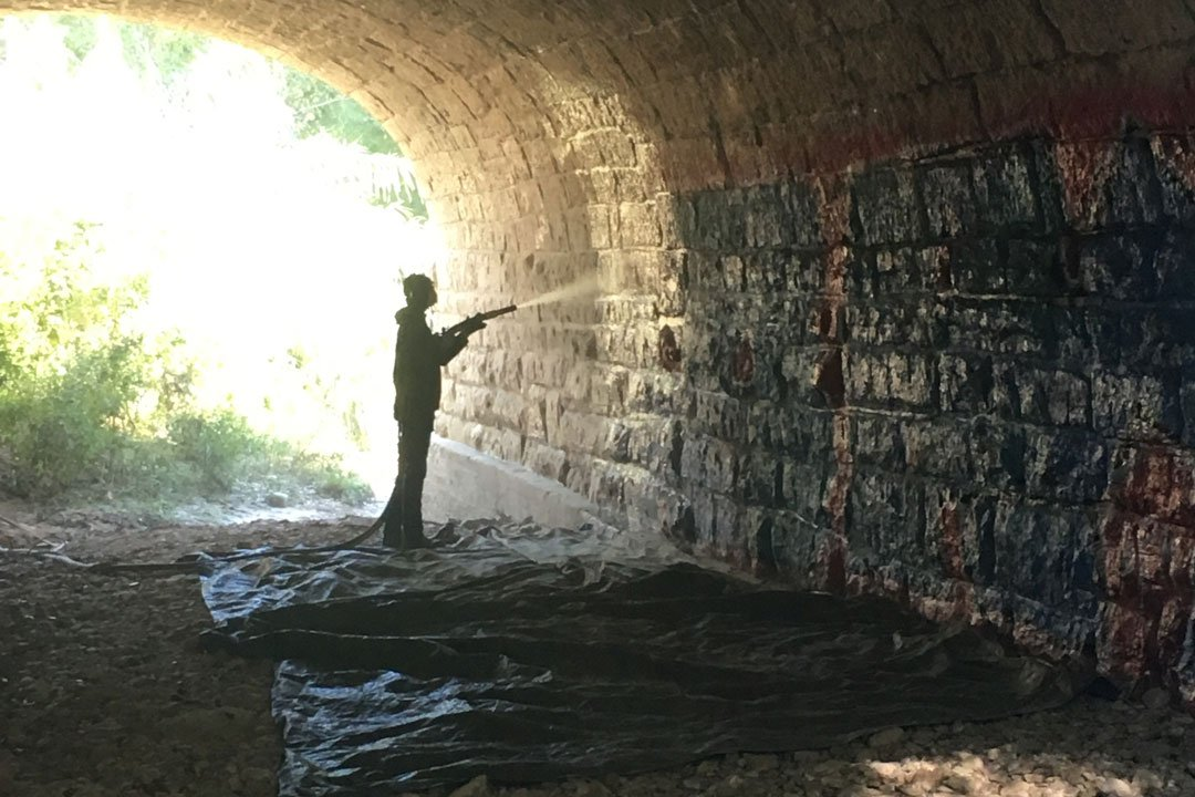 removing graffiti under a historic stone bridge