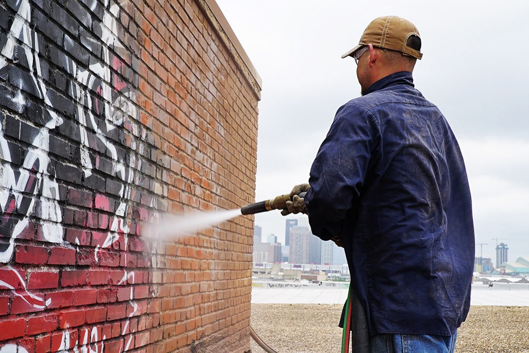 man removing graffiti from a rooftop structure in houston