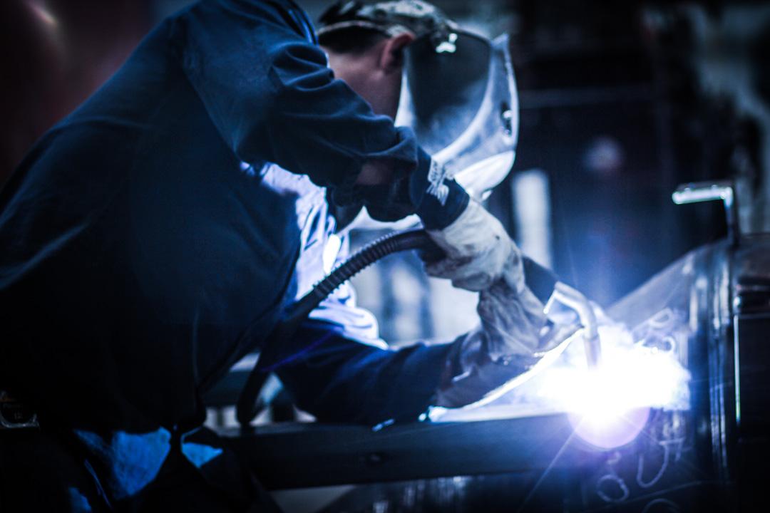 welder in dark warehouse manufacturing blast equipment