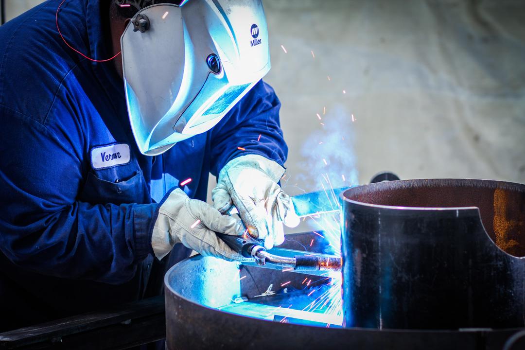 welder manufacturing an abrasive blast pot