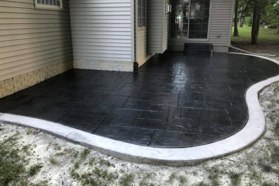dark grey stained stamped concrete patio