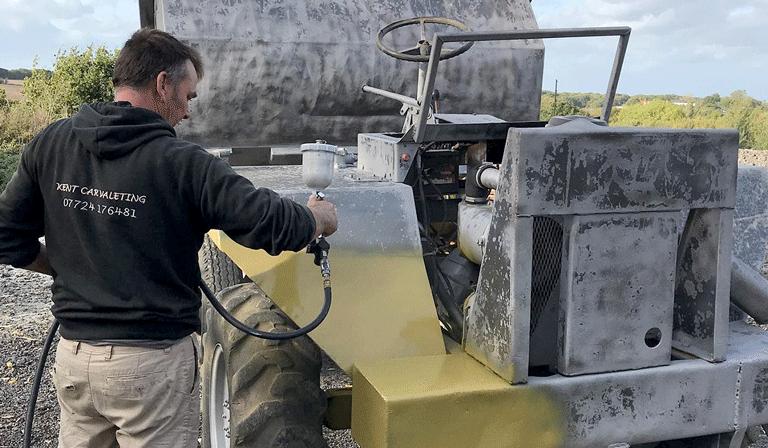 spraying yellow paint onto freshly blasted equipment